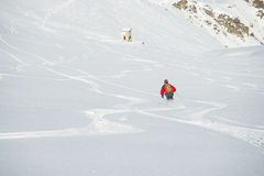 Freeriding on fresh powder snow. One person skiing downhills off piste on snowy slope in the italian Alps, with bright sunny day of winter season. Thick Powder Stock Photography