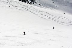 Freeriding. Skiers during a downhill ride in the mountains. stock image