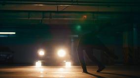Freerunner del giovane che fa i salti acrobatici su parcheggio sotterraneo video d archivio