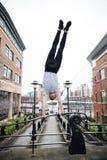 Freerunner que hace una posición del pino en la ciudad Fotografía de archivo