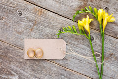 Freesia with blank tag and wedding rings Royalty Free Stock Photo