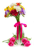 Freesia and daffodil  flowers. Blue, pink  and yellow freesia   flowers in glass vase   isolated on white background Stock Photo