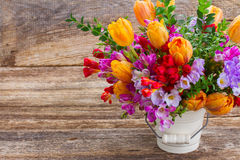 Freesia and  flowers. Fresh blue, violet  and red freesia and orange tulip flowers  on wooden background Royalty Free Stock Photography