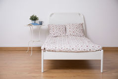 Freestanding bed in teen room. White freestanding bed in cozy teen room royalty free stock photo
