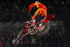 Freestyle. A freestyle moto-x rider goes through a trick during an indoor competition Stock Images