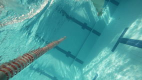 FREESTYLE: An athlete is swimming in a swimming pool (underwater view - action cam). FREESTYLE: An athlete is swimming in a swimming pool (underwater - action stock footage