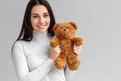 freestyle Condizione della donna su grigio con l'orsacchiotto che guarda il primo piano felice della macchina fotografica fotografia stock