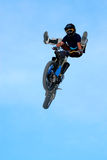 Freestyle on cross. Motocross rider going over the jump blue sky background Royalty Free Stock Photos