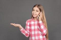 freestyle Dziewczyny pozycja odizolowywająca na popielaty opowiadać na smartphone ono uśmiecha się zadumany zdjęcia stock
