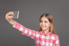freestyle Dziewczyny pozycja odizolowywająca na popielatym bierze selfie na smartphone przyglądającej kamerze rozochoconej zdjęcie stock