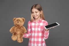 freestyle Dziewczyny pozycja odizolowywająca na popielatym wybiera misiu zamiast cyfrowej pastylki szczęśliwej zdjęcia stock