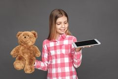 freestyle Dziewczyny pozycja odizolowywająca na popielatym z misiem wybiera cyfrową pastylkę radosną zdjęcia royalty free