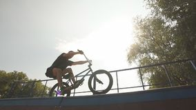 freestyle El jinete de BMX resbala en la bici en rampa en parque del patín Cultura de la calle almacen de metraje de vídeo