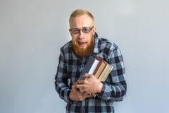 freestyle Homem maduro nos monóculos que estão isolado no sorriso de aperto cinzento dos livros nerdy imagem de stock