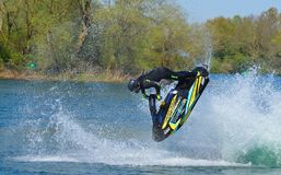 Freestyle Jet Skier  competitor  performing back flip creating at lot of spray. Royalty Free Stock Photos