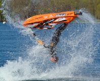 Freestyle Jet Skier  competitor upside down  performing back flip creating at lot of spray. Stock Photos