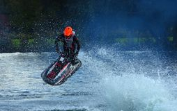 Freestyle Jet Skier performing Jump  creating at lot of spray. Stock Photo
