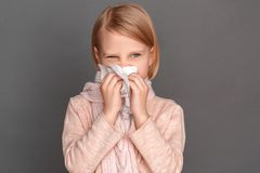 Freestyle. Little girl in scarf isolated on grey blowing nose into tissue looking aside concerned close-up stock photos