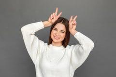 freestyle Młodej dziewczyny pozycja odizolowywająca na popielatym seansie uzbrajać w rogi uśmiechniętego figlarnie zakończenie--w zdjęcie stock