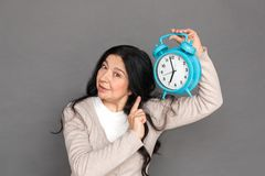 Freestyle. Mature lady standing isolated on grey shwoing time on alarm clock concerned. Mature woman standing isolated on grey wall holding alarm clock up stock image