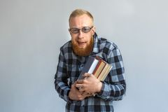 Freestyle. Mature man in eyeglasses standing isolated on grey hugging books smiling nerdy stock image