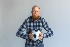Freestyle. Mature man standing isolated on grey with ball holding breath diligently stock image