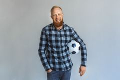 Freestyle. Mature man standing isolated on grey with ball smiling relaxed royalty free stock photo