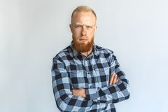 Freestyle. Mature man standing isolated on grey crossed arms looking camera confused close-up royalty free stock photo