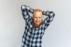 Freestyle. Mature man standing isolated on grey hands behind head laguhing playful stock photography