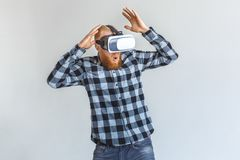 Freestyle. Mature man in virtual reality headset standing isolated on grey playing hands up surprised. Red hair mature man wearing virtual reality headset royalty free stock images