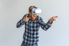 Freestyle. Mature man in virtual reality headset standing isolated on grey playing shooting with imaginary gun. Red hair mature man wearing virtual reality royalty free stock photos