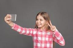 freestyle Meisje die op grijs wordt zich geïsoleerd bevinden die die selfie op smartphone nemen die gelukkig vredesgebaar tonen stock afbeeldingen