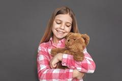 freestyle Meisje status geïsoleerd op grijs die teddybeer gelukkig close-up koesteren royalty-vrije stock foto's