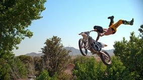 Freestyle motocross biker performs the trick in jump at fmx competitions stock photos