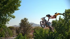 Freestyle motocross biker performs the trick in jump at fmx competitions stock image
