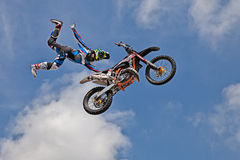 Freestyle motocross show. A stunt biker make a jump and performing an acrobatic figure in flight, during the motorcycle rally Motosalsicciata 2016 on April 10 royalty free stock image