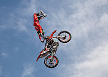 Freestyle motocross show. A stunt biker make a jump and performing an acrobatic figure in flight, during the motorcycle rally Motosalsicciata 2016 on April 10 stock photo