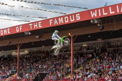 Freestyle motocross team member launches off ramp into the air during performance. Williams Lake, British Columbia/Canada - July 2, 2016: Global FMX Professional Royalty Free Stock Photo