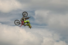 Freestyle Motocross trick Head overturn with the motorcycle on background of the blue cloud sky. German-Stuntdays, Zerbst - 2017,. Freestyle Motocross trick Head Stock Image
