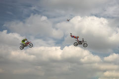 Freestyle Motocross trick Head overturn of two motorcyclists on background of the blue cloud sky. German-Stuntdays, Zerbst - 2017, Royalty Free Stock Images