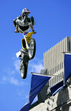 Freestyle Motorcycle Jumping. A motorcyclist is jumping in freestyle. Designs on clothings, booths, helmet and gloves have been re-arranged to hide their origins Royalty Free Stock Photography