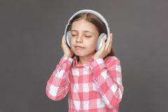 freestyle Muchacha en los auriculares que se colocan aislados en gris que escucha el primer alegre de los ojos cerrados de la mús fotos de archivo