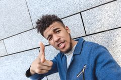 Freestyle. Mulatto guy standing isolated on wall taking selfie pointing at camera cool close-up stock images