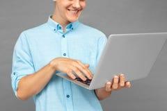 freestyle Nastolatek chłopiec pozycja odizolowywająca na popielatych wyszukuje środkach na laptopie rozochoconym w górę obraz royalty free