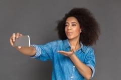 freestyle Oliwkowa kobiety pozycja na popielatym bierze selfie na smartphone dosłania buziaku kamera figlarnie obraz stock