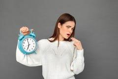 freestyle Position de jeune fille sur le gris avec clockshowing le geste en difficulté photos stock