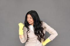 freestyle Señora madura en los guantes de goma que se colocan aislada en la mano gris en las caderas que muestran el puño confiad imagen de archivo libre de regalías