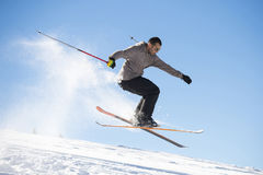 Freestyle ski jumper with crossed skis. In snowy mountains Royalty Free Stock Photo