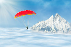 Freestyle solo paragliding over clouds against mountain peak Stock Photo