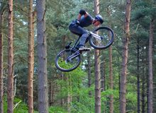 Freestyle Stunt Cyclist in mid air very high with trees in background. HAYNES, BEDFORDSHIRE, ENGLAND - MAY 14, 2017: Freestyle Stunt Cyclist in mid air very Royalty Free Stock Photography